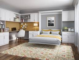 Murphy bed office White Office Space With White Shelving Cabinets Built In Desk And Murphy Bed With Deep Yellow Accents California Closets Murphy Beds Wall Bed Designs And Ideas By California Closets