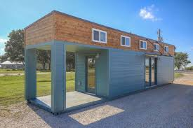 A covered porch has been carved from the shipping container. All photos via  Tiny House Listings