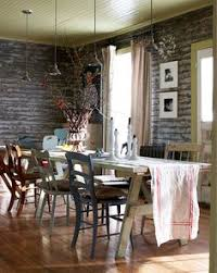cool looking walls and a nice cal table set up with a mismatched variety of chairs make a charming dining room