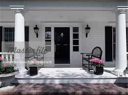 exteriors close up of porch white and black symmetric black benches with pink geranium on either side of front door sidelights columns stock photo