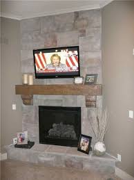 stone faced electric fireplace with beam and tv above more