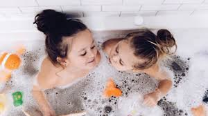 in a bubble bath with lots of tub toys