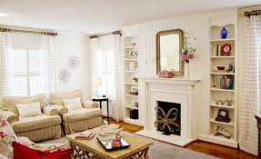 trend design living room ideas decorate style white painted wall white curtain window white wall shelves mirror fireplace armchair wooden coffee table gray