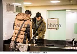 public bathroom mirror. Reflection Of Young Man Washing Hands In Public Bathroom - Stock Image Mirror U