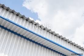 industrial construction of metal white sheet and blue corners roof sheet metal or corrugated roofs of factory building or warehouse