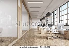 pictures of an office. front view of an office interior with a row dark wood tables standing under large pictures c