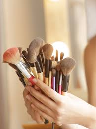 woman in towel holding makeup brushes