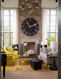 black and yellow living room features a two story ceiling lined with a glass globe modular chandelier illuminating a two story stone fireplace lined with a