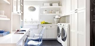 Amazing white and gray laundry room with white beadboard cabinets paired  with white quartz countertops and light gray subway tile backsplash.