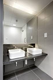 public bathroom mirror. backlit mirror simple yet modern commercial bathroom sinks - plain white on a black counter with silver fixtures are basic enough but closer look public
