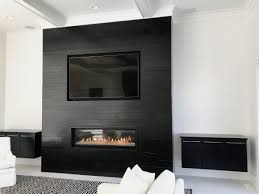 norstone planc large format tiles in ebony installed on a modern fireplace with linear gas insert