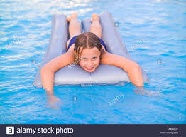 SPAIN IBIZA 10 YEAR OLD GIRL CHILD WOMAN FEMALE LYING ON LILO INFLATABLE  AIR MATTRESS IN SWIMMING POOL SMILING HAPPY FUN PLAY WATER SUMMER SUN COOL