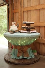 Wooden spool with icicle lights covered with round table cloth. Used a  bungee cord to