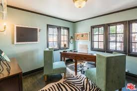 the home office features green walls and seats along with a hardwood flooring and a stylish