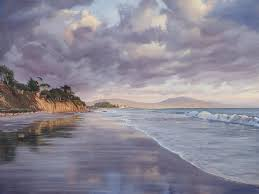 dramatic clouds light up purple from the last rays of sun and reflect onto the wet sand on santa barbara s east beach