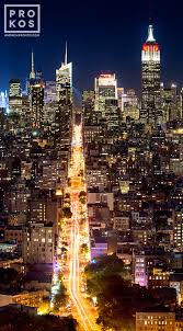 a vertical cityscape photograph of new york city at night as seen from soho limited