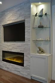 fireplace tv combo one end of fireplace wall with custom cabinetry erthcoverings silver fox stone and dimplex electric fireplace design by stylish