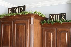 greenery on top of kitchen cabinets on top of stairs