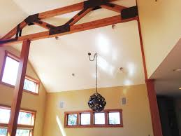sloped ceiling with dark wine barrel chandelier and faux ceiling beams and white paint wall plus wooden wine barrel chandelier also wine barrel stave