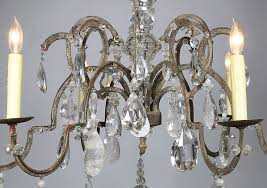 a rare french 19th 20th century louis xv style six light patinated metal and rock crystal chandelier the thin metal frame surmounted with six s scrolled