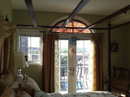 a fl stained glass transom is pictured above the door in a bedroom