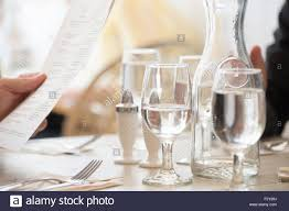 glasses table setting. Close Up Of Wine And Water Glasses Place Settings At A Table In Restaurant. Person\u0027s Hand Holding The Menu. Setting