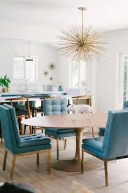peacock blue leather tufted dining chairs with oval dining table and brass sputnik chandelier