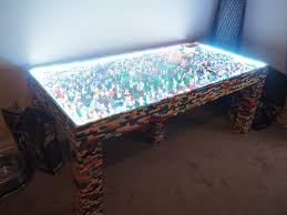the table itself is made from wood but has been covered by countless lego bricks beneath its glass top are more than 250 minifigures and other lego pieces