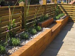 building garden beds. intermittent benches along the fence add interest to these flower beds building garden