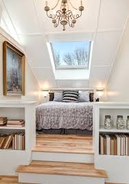 two tier attic master bedroom in design with light wood floors built bookshelves and large skylight white walls small