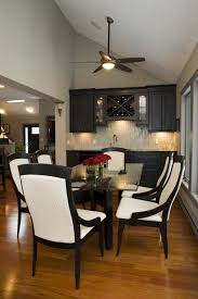 a gl table is flanked by six curved leather black and white chairs and filled with two gl vases of red roses in this traditional formal dining room