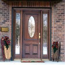 interior brown wooden door with oval glass on the middle placed between narrow glass windows