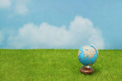 Blue Globe On Green Grass Over Blue Sky Background Stock Photo