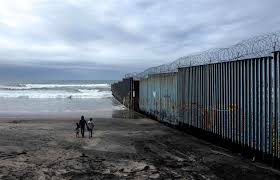 image a family of migrants walk on the beach near the u s mexico border