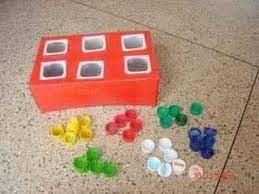 Una caja de cartón, unos envases de yogur vacíos, y unos tapones de colores. Un Juego Matematico Con Material Reciclado Actividades Infantil