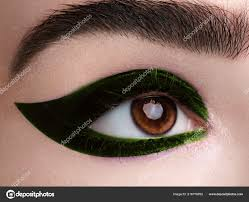 woman appling black eye liner fashion makeup with perfect arrows shape with bright green eyeshadows color cosmeticake up photo by