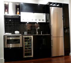 kitchen black glossy kitchen cabinet and black tile backsplash connected by white refrigerator on the