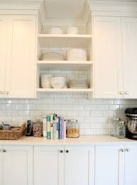 the best white or off white paint colours for cabinets include cloud white shown in kitchen with subway tile backsplash and open shelves and white