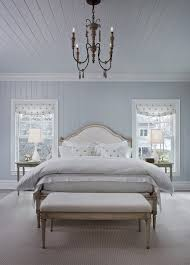 chic beachstyle bedroom blue and white pillows collection of carved wood chandelier and off white