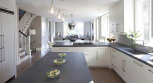 g shaped kitchen with contemporary white cabinets accented with brushed nickel pulls alongside dark gray concrete counters with a mini brick marble