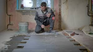 the worker in the building form checks the level of the surface on the ceramic tile