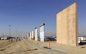 image people look at prototypes of a border wall