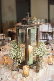 a wooden candle lantern surrounded with baby s breath and candles