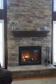 gorgeous gray stone fireplace mantel idea with black cedar design above black framed door with concrete