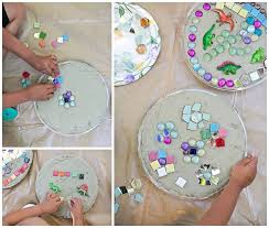 give the kids each a mold filled with concrete and have them immediately place their designs on top making sure to press each stone tile object firmly in