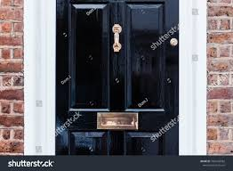 black wooden front house door with a gold letter box and a handle