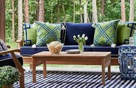 Patio features a teak sofa lined with blue cushions with white piping lined  with green and blue pillows facing a teak coffee table atop a blue striped  rug.