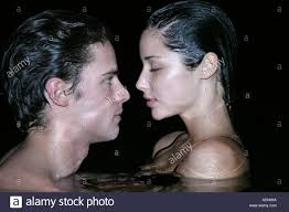 young couple look pionately into each others eyes while swimming at night