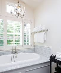 chandelier over bathtub in bright white bathroom