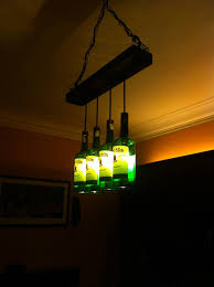 29 year old radiologist ahmed ghoneim creates exuberant lighting fixures and chandeliers out of used materials like alcohol bottles recycling them for